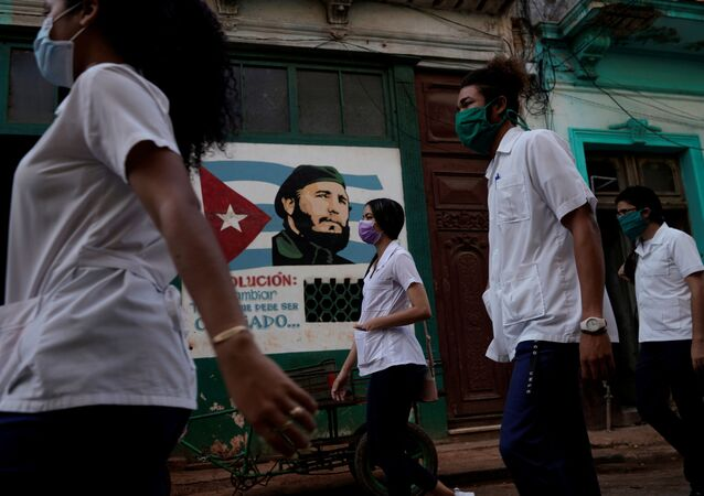 Medical students walk past an image of late Cuban President Fidel Castro as they check door to door for people with symptoms amid concerns about the spread of the coronavirus disease (COVID-19), in downtown Havana, Cuba, May 12, 2020.