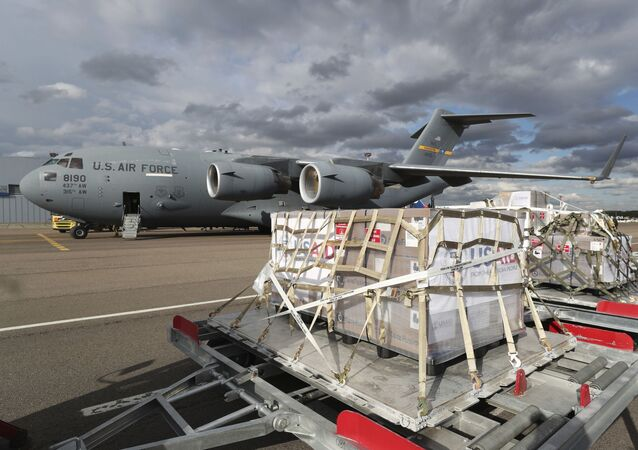 A tractor pulls the first batch of medical aid from the United States, including 50 ventilators as a donation to help the country tackle the coronavirus outbreak, from a US Air Force C-17 Globemaster transport plane upon its landing at Vnukovo International Airport outside Moscow, Russia, 21 May 2020.