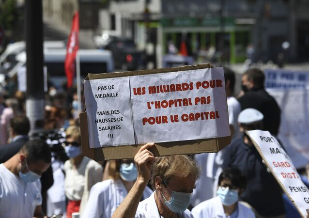 Parisian Healthcare workers hold a placard reading billions for hospitals, not for the capital as they gather during a demonstration in front of the Robert Debre hospital to call for better working conditions and an increase of manpower as French government launched general talks on Health, on May 28, 2020, in Paris