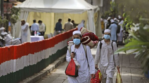 Muslim pilgrims walk towards a bus that will take them to a quarantine facility, amid concerns over the spread of the new coronavirus, at the Nizamuddin area of New Delhi, India, Tuesday, March 31, 2020 - Sputnik International