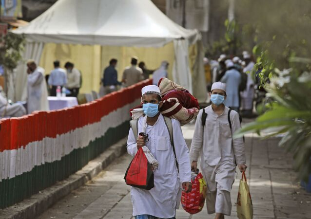 Muslim pilgrims walk towards a bus that will take them to a quarantine facility, amid concerns over the spread of the new coronavirus, at the Nizamuddin area of New Delhi, India, Tuesday, March 31, 2020