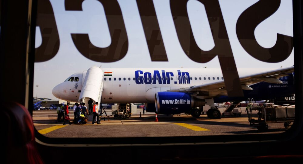 An airplane belonging to the Indian airline GoAir can be seen from this image taken through the glass of an airport bus at the Indira Gandhi International Airport in New Delhi on October 5, 2015