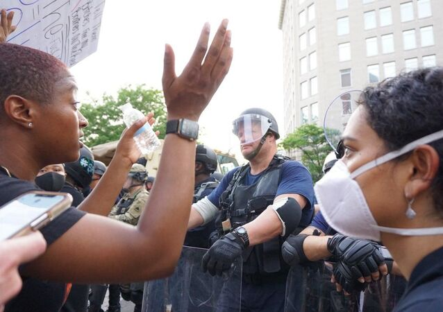 People and police during protests in Washington DC on 3 June 2020