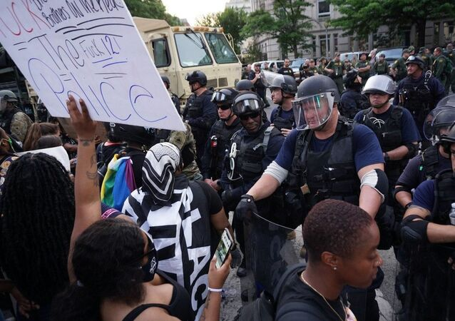 Protesters stand in front of riot police in Washington DC on 3 June 2020
