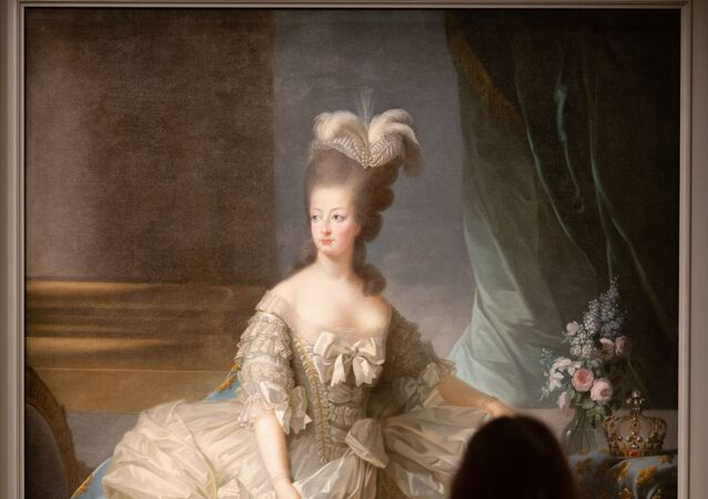 A visitor looks at a painting representing French queen Marie-Antoinette entitled Marie-Antoinette en grand habit (Marie-Antoinette in court dress, 1779-1788) by Elisabeth Vigee Le Brun displayed at Marie-Antoinette, Metamorphoses of an image exhibition at the Conciergerie Paris museum, on October 15, 2019