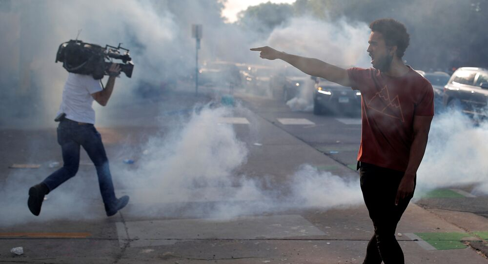 A protester argues with law enforcement officers as a reporter runs away from tear gas during a demonstration against the death in Minneapolis police custody of George Floyd, in Saint Paul, Minnesota, U.S. May 31, 2020.