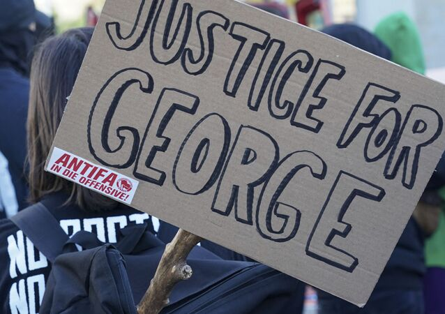 A poster with the inscription 'Justice for George' and 'Antifa on the offensive' is held by a protestor during a demonstration under the motto Youth Day - Fight for your future
