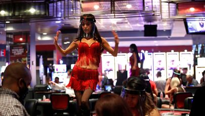 A woman wears a face shield as she dances behind blackjack tables during the reopening of The D hotel-casino, closed by the state since March 18, 2020 as part of steps to slow the spread of the coronavirus disease (COVID-19), in downtown Las Vegas, Nevada, U.S. June 4, 2020.