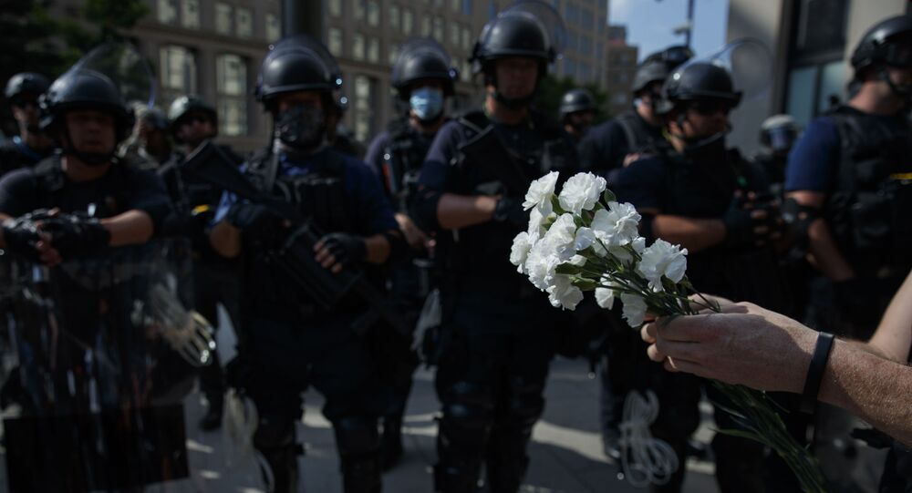 A demonstrator holds flowers as to place at the feet of a line of military near the White House to protest the death of George Floyd, Wednesday, June 3, 2020, in Washington