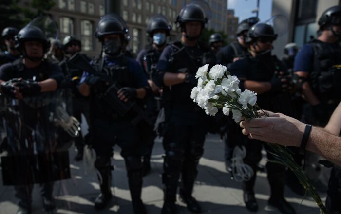 A demonstrator prepares to place flowers at the feet of a line of military troops near the White House to protest the death of George Floyd, 3 June 2020, in Washington, DC.