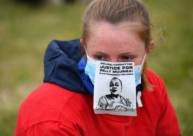 A woman wearing a face mask with a Justice For Belly Mujinga message is seen in Hyde Park during a Black Lives Matter protest following the death of George Floyd who died in police custody in Minneapolis, London, Britain, June 3, 2020