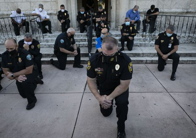Police officers kneel during a rally in Coral Gables, Florida on May 30, 2020 in response to the recent death of George Floyd, an unarmed black man who died while being arrested and pinned to the ground by a Minneapolis police officer.