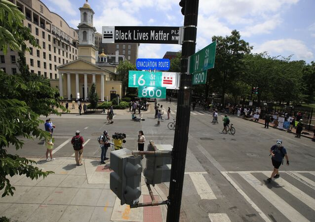With St. John's Church in the background, people walk under a new street sign on Friday, June 5, 2020, in Washington. The section of 16th street in front of the White House is now officially 'Black Lives Matter Plaza,' District of Columbia Mayor Muriel Bowser tweeted. The black and white sign was put up to mark the change