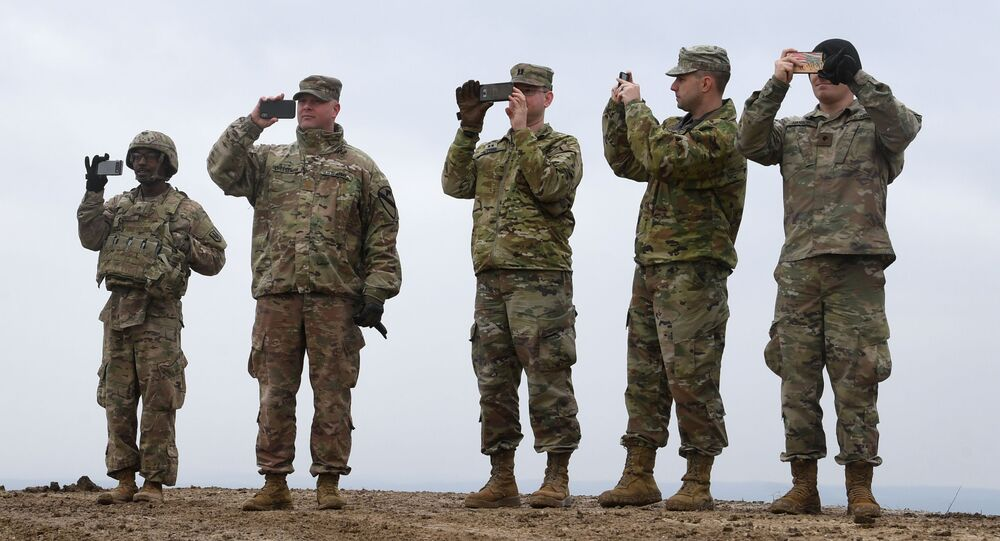 US soldiers take pictures with their cell phones during an artillery live fire event by the US Army Europe's 41st Field Artillery Brigade at the military training area in Grafenwoehr, southern Germany, on March 4, 2020.