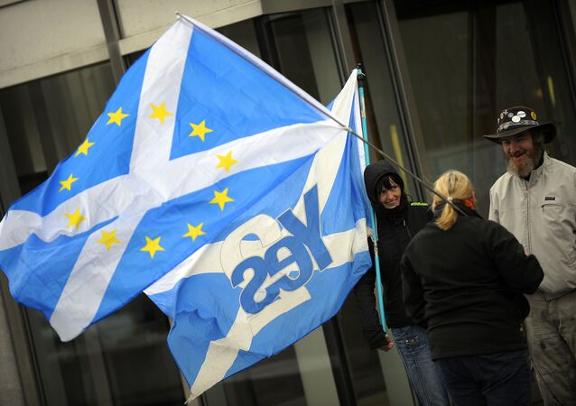 This picture shows pro-independence campaigners with one holding a 'yes' to independence flag and another holding a Saltire flag with EU logo design, outside the Scottish Parliament b