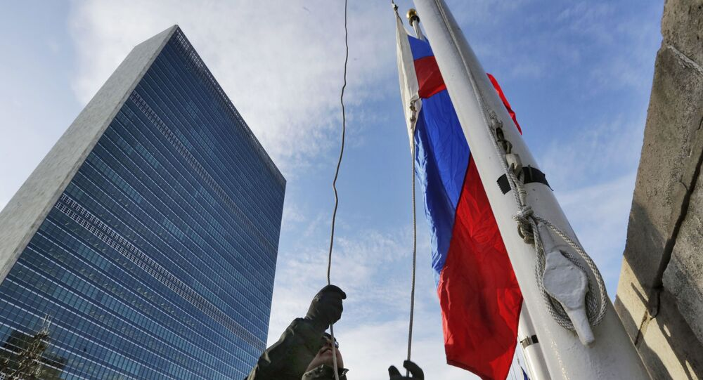 A United Nations security officer raises the Russian flag outside U.N. headquarters, Tuesday morning, Feb. 21, 2017.