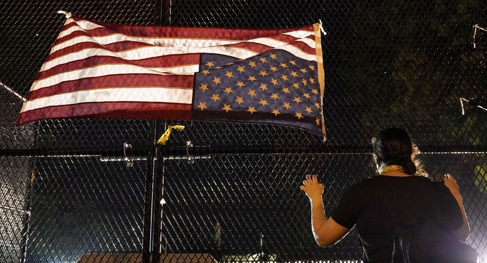 A demonstrator looks on next to an upside-down American flag at a fence in front of the White House, during a protest against the death in police custody of George Floyd, in Washington, U.S., June 4, 2020.