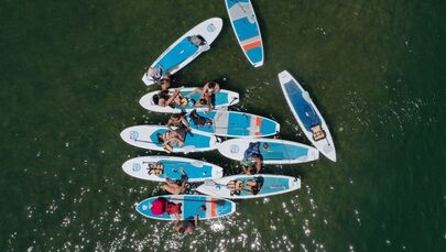 In this aerial view from a drone, residents paddle board and kayak in Lady Bird Lake on 20 May 2020 in Austin, Texas. Texas Governor Greg Abbott announced that bars, wine tasting rooms, bowling alleys, skating rinks, bingo halls, aquariums, and equestrian events will be allowed to open on Friday, 22nd May despite a surge in confirmed coronavirus (COVID-19) cases in the state.