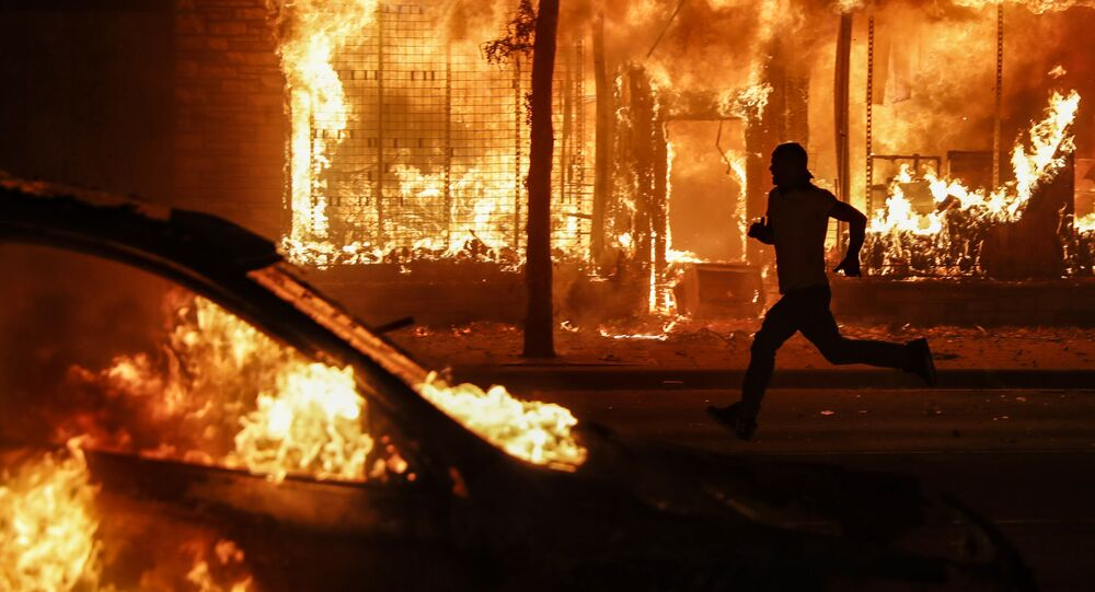 A protester runs past burning cars and buildings on Chicago Avenue, Saturday, May 30, 2020, in St. Paul, Minn. Protests continued following the death of George Floyd, who died after being restrained by Minneapolis police officers on Memorial Day.