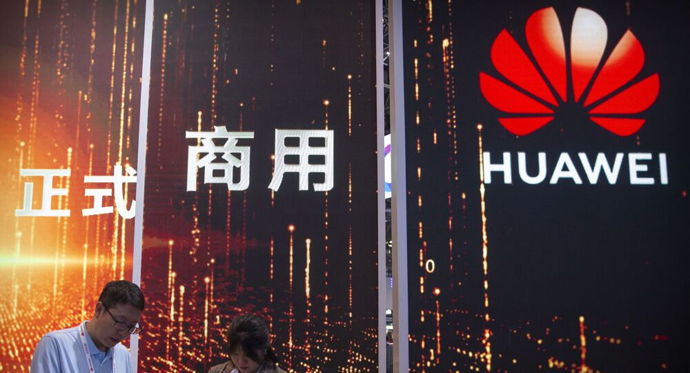 In this Oct. 31, 2019 photo, attendees use their smartphones near a Huawei booth at the PT Expo technology conference in Beijing. Chinese tech giant Huawei is racing to develop replacements for Google apps. U.S. sanctions imposed on security grounds block Huawei from using YouTube and other popular Google core apps.