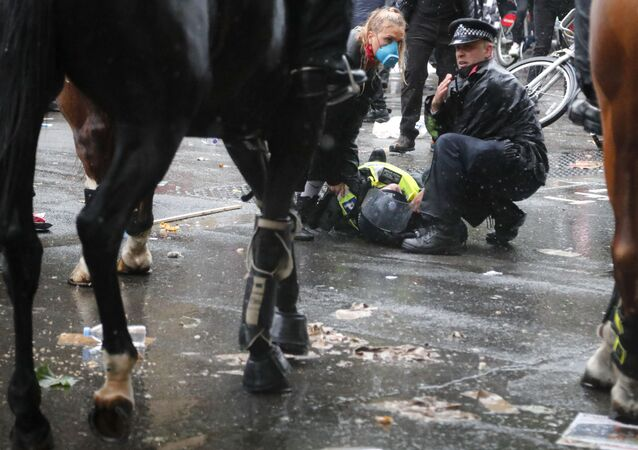 A colleague attends to a police officer who was injured when falling of a horse during scuffles with demonstrators at Downing Street during a Black Lives Matter march in London, Saturday, June 6, 2020, as people protest against the killing of George Floyd by police officers in Minneapolis, USA.