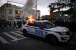 A NYPD police car is set on fire as protesters clash with police during a march against the death in Minneapolis police custody of George Floyd, in the Brooklyn borough of New York City, U.S., May 30, 2020.