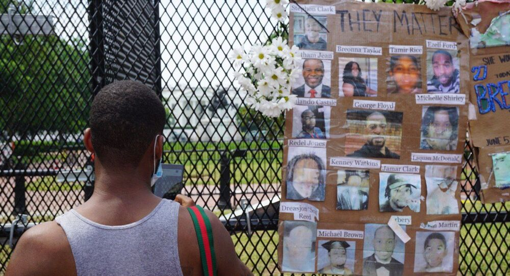 A man stands next to photos of victims of police brutality displayed on a metal fence during a protest near the White House in Washington DC, US, 06.06.2020.