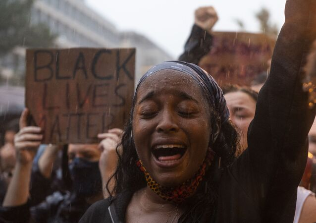 A protester shouts Black Lives Matter during a rain storm in front of Lafayette Park next to the White House, Washington, DC on June 5, 2020.