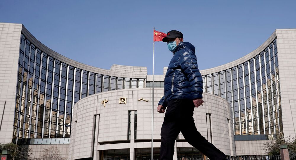 A man wearing a mask walks past the headquarters of the People's Bank of China, the central bank, in Beijing, China, as the country is hit by an outbreak of the new coronavirus, February 3, 2020.