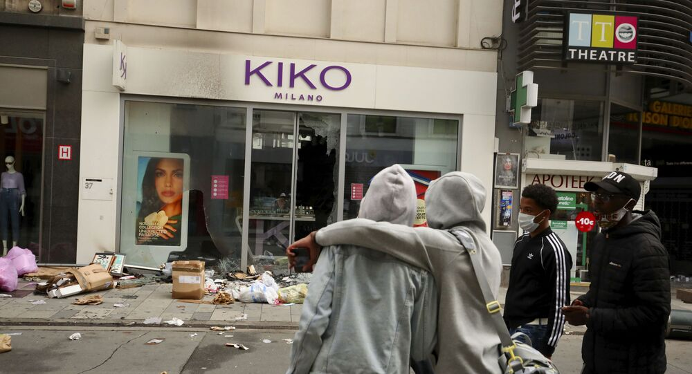 Two boys look at a shop after its windows were broken after a Black Lives Matter protest rally in Brussels, Sunday, June 7, 2020.