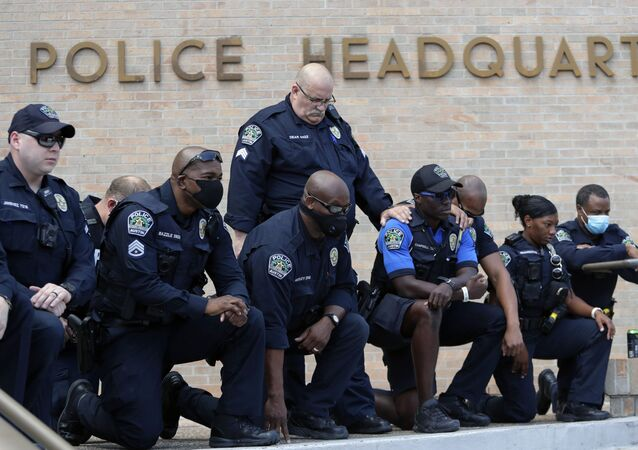 Members of the Austin Police Department kneel in front of demonstrators who gathered in Austin, Texas, Saturday, June 6, 2020, to protest the death of George Floyd, a black man who was in police custody in Minneapolis. Floyd died after being restrained by Minneapolis police officers on Memorial Day.