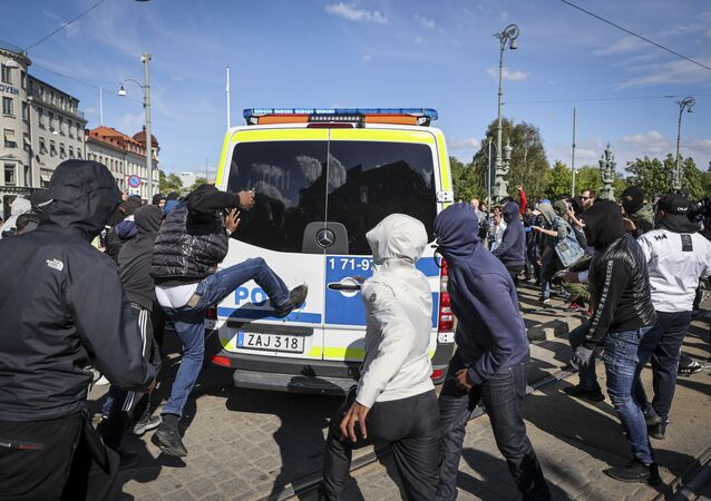 Demonstrators attack a police car during a anti-racism demonstration on June 7, 2020 in Gothenburg, Sweden, in solidarity with protests raging across the US over the death of George Floyd, an unarmed black man who died during an arrest on May 25.