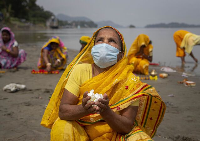 Hindu women perform rituals during a prayer ceremony to rid the world of coronavirus, on the banks of the river Brahmaputra in Gauhati, India, Friday, June 5, 2020