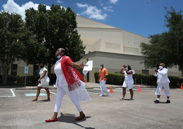 A prayer group walks the grounds of the Fountain of Praise church where services will be held for George Floyd on June 7, 2020 in Houston, Texas