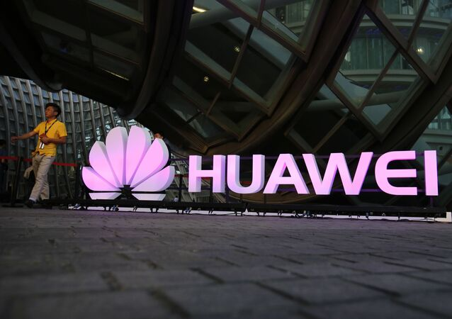 People walk past an illuminated logo for Huawei at a launch event for the Huawei MateBook in Beijing, Thursday, May 26, 2016
