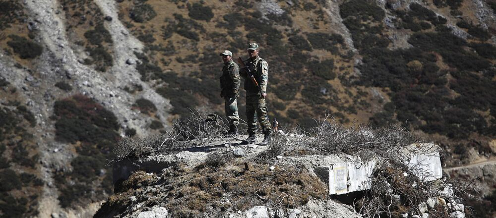 Indian army soldiers keep watch on a bunker at the Indo China border in Bumla at an altitude of 15,700 feet (4,700 meters) above sea level in Arunachal Pradesh, India, Sunday, Oct. 21, 2012