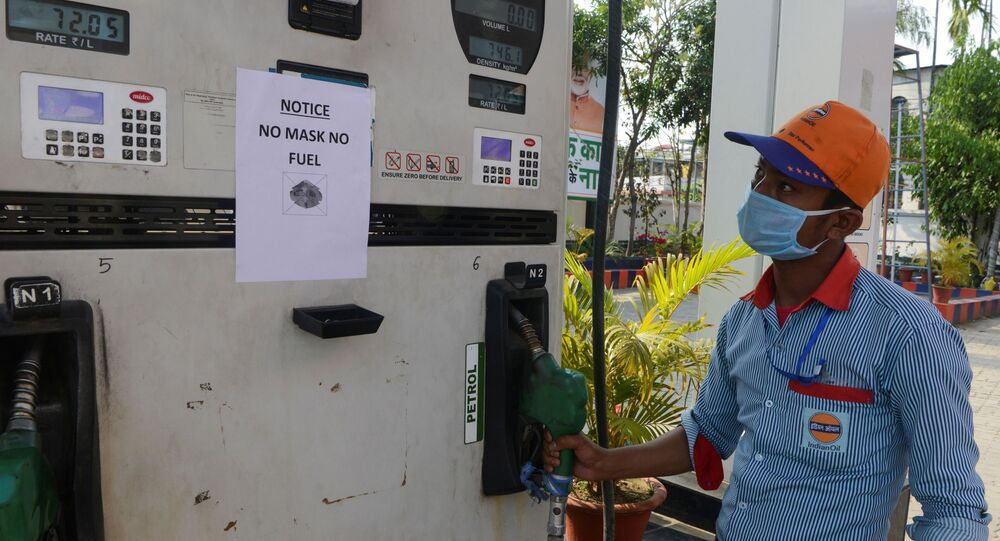 An employee stands near a notice reading 'No Mask No Fuel' at a gas station during a government-imposed nationwide lockdown as a preventive measure against the COVID-19 coronavirus in Siliguri on March 28, 2020. (Photo by Diptendu DUTTA / AFP)