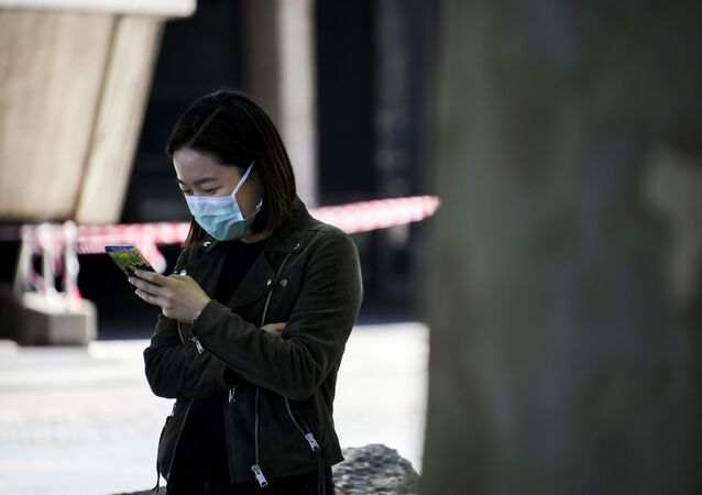 A woman wearing a face mask looks at her phone on the south bank of the river Thames, as the lockdown due to the coronavirus outbreak continues, in London, Saturday, April 25, 2020.
