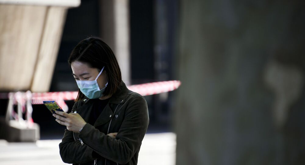 A woman wearing a face mask looks at her phone on the south bank of the river Thames, as the lockdown due to the coronavirus outbreak continues, in London, Saturday, 25 April 2020.