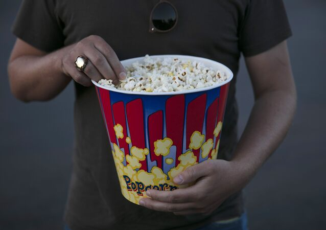 A moviegoer eats popcorn at Mission Tiki drive-in theater in Montclair, Calif., Thursday, May 28, 2020.
