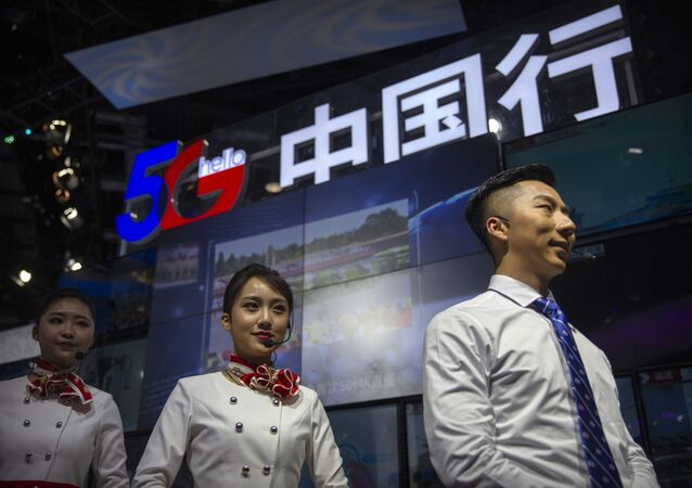 Staff members stand at a display for 5G services from Chinese technology firm China Telecom at the PT Expo in Beijing, Thursday, Oct. 31, 2019.