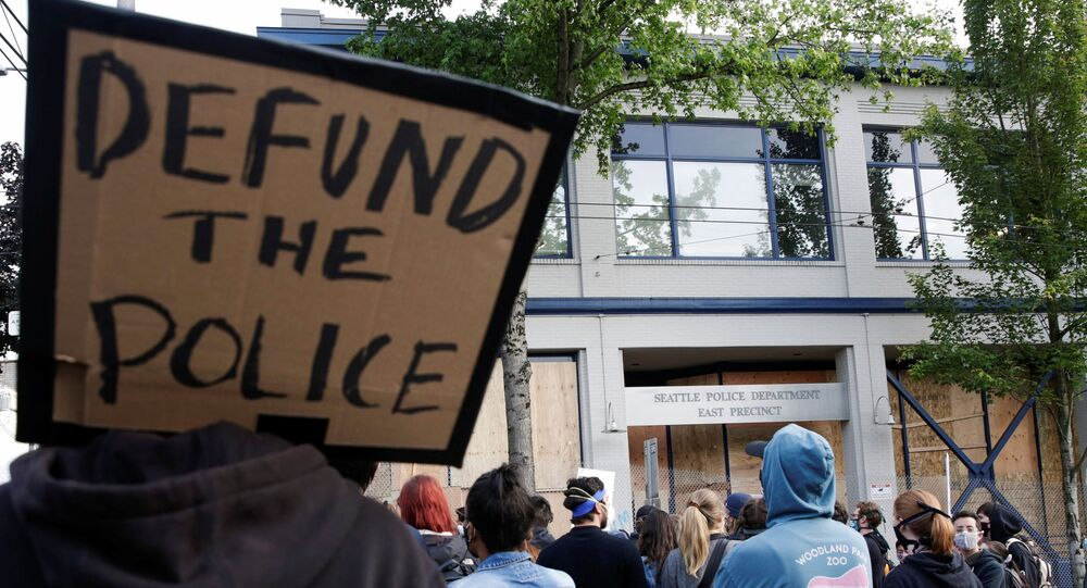 A protester holds a sing that reads defund the police after Seattle Police vacated the department's East Precinct and people continue to rally against racial inequality and the death in Minneapolis police custody of George Floyd, in Seattle, Washington, U.S. June 8, 2020.