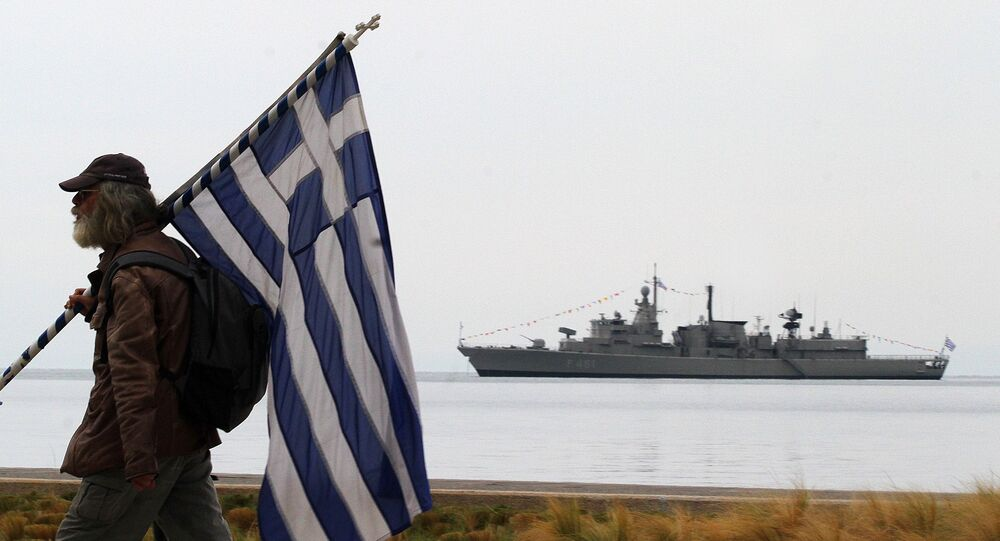 A spectator holds a Greek flag as a Greek Navy vessel is moored at Thermaikos Gulf during the annual military parade in the northern Greek port city of Thessaloniki on Tuesday, Oct. 28, 2014