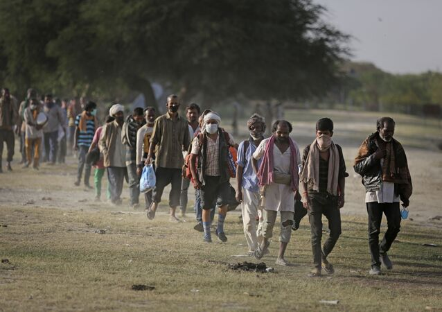 Indian migrant laborers and homeless people walk towards a bus as they are being evicted from the banks of Yamuna River where they have been squatting during lockdown in New Delhi, India, Wednesday, April 15, 2020