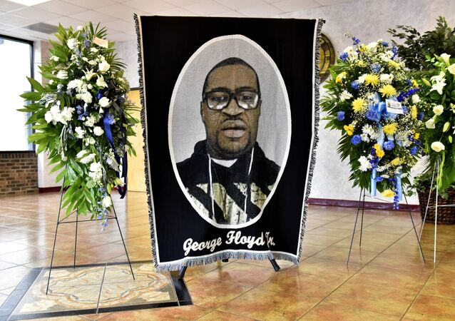 A picture of George Floyd and flowers are set up for a memorial service for Floyd, Saturday, June 6, 2020, in Raeford, N.C. Floyd died after being restrained by Minneapolis police officers on May 25