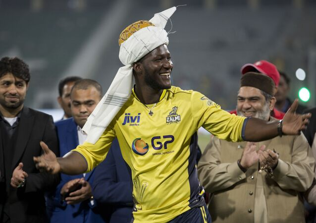 Former West Indies captain Darren Sammy gestures wearing a traditional turban at Gaddafi stadium in Lahore, Pakistan, Sunday, March 5, 2017