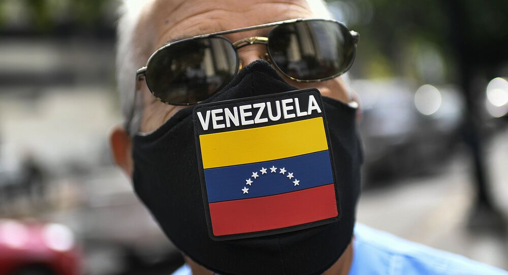 A man wears a face mask with the Venezuela flag, amid the spread of the new coronavirus, as he waits for hours to fill up his car at a state-run oil company PDVSA as station in Caracas, Venezuela, Monday, May 25, 2020
