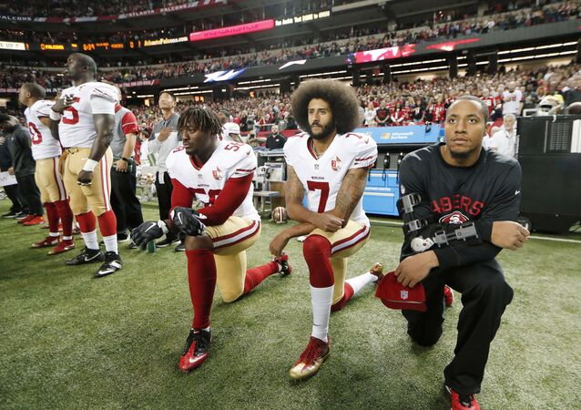 In this Dec. 18, 2016, file photo, San Francisco 49ers quarterback Colin Kaepernick (7) and outside linebacker Eli Harold (58) kneel during the playing of the national anthem before an NFL football game against the Atlanta Falcons in Atlanta