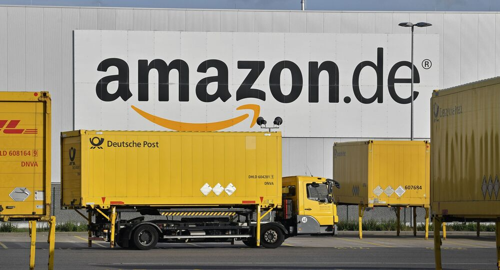 FILE - In this file photo dated Wednesday, Nov. 14, 2018, post trucks leave the Amazon Logistic Center in Rheinberg, Germany