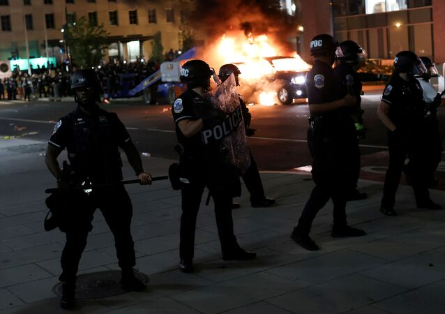 Police officers look on as a car burns in the back as protesters continue to rally against the death in Minneapolis police custody of George Floyd, near the White House, in Washington, U.S., May 30, 2020.